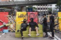 16.11.2019, China, Hongkong: Demonstranten sitzen auf einem Sofa, während Bewohner Barrikaden in der Nähe der Universität von Hongkong (HKU) entfernen. Foto: Miguel Candela/SOPA Images via ZUMA Wire/dpa +++ dpa-Bildfunk +++