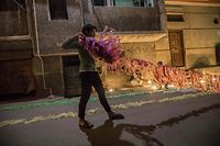 An Egyptian youth takes part in decorating his residential street in preparation for the Muslim holy month of Ramadan in Cairo's Hadayek el-Maadi district, on April 21, 2020. - From cancelled iftar feasts to suspended mosque prayers, Muslims across the Middle East are bracing for a bleak month of Ramadan fasting as the threat of the COVID-19 pandemic lingers. Ramadan is a period for both self-reflection and socialising. Believers fast from dawn to dusk and then gather around a family or community meal each evening of Islam's holiest month, which begins later this week and ends with Eid al-Fitr festivities (Photo by Khaled DESOUKI / AFP)