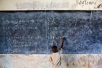 ARCHIV - 26.09.2013, Burundi, Rumonge: In einer Schule löst ein Junge Mathematikaufgaben an der Tafel. Weltweit wird an unterschiedlichen Tagen, in Deutschland am 20. September, gefeiert, um auf Probleme und Nöte der Kinder vor allem in den Entwicklungsländern aufmerksam zu machen. Die UN begehen den 1954 angeregten Weltkindertag am 20. November. Foto: Thomas Schulze/zb/dpa +++ dpa-Bildfunk +++
