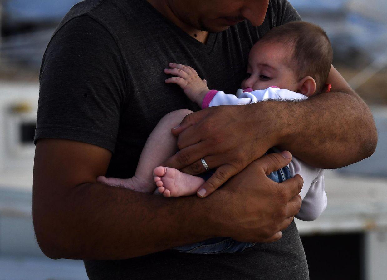 Ein Kurde hält ein Baby in einem Flüchtlingslager im Arm. Viele Kurden, die aus Syrien in den Irak geflohen sind, berichten von Beschuss durch türkische Streitkräfte.