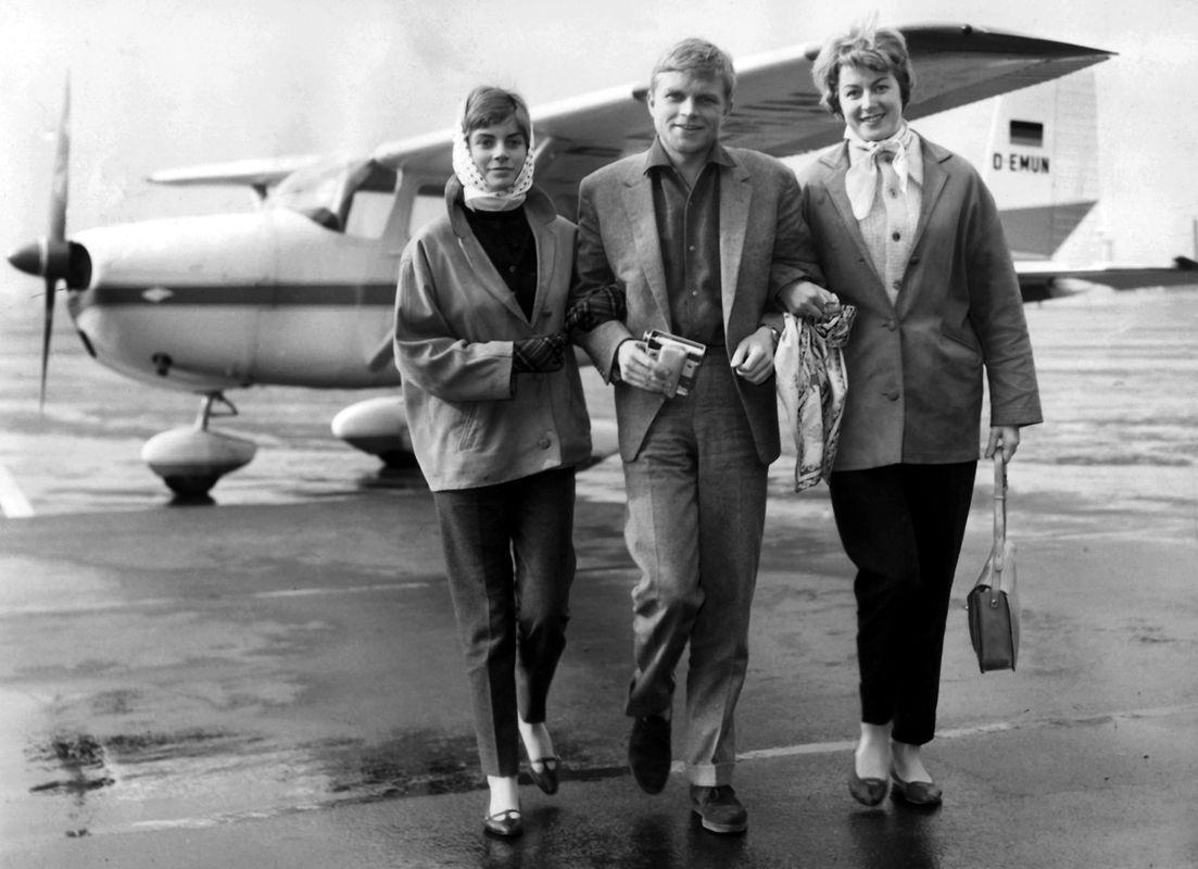 Der Schauspieler Hardy Krüger mit seiner Frau Renate (r) und Tochter Christiane kurz nach ihrer Ankunft auf dem Flughafen in Croydon (Surrey) in England im März 1959. Im Hintergrund steht seine Cessna.