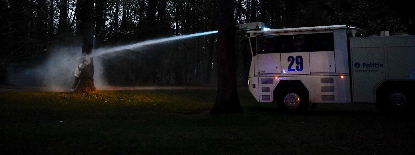 Ein Demonstrant geht am Freitag im Bois de la Cambre in Brüssel vor einem Polizeiwasserwerfer in Deckung.