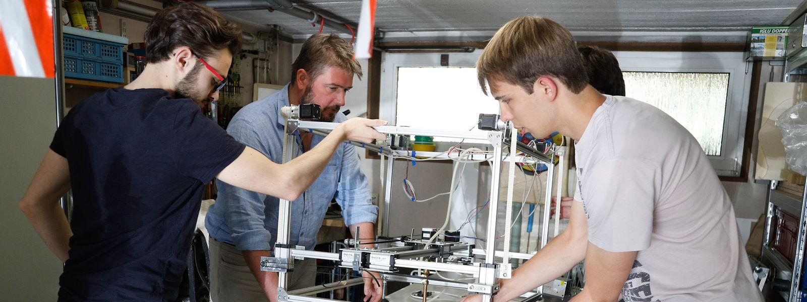 Lehrer Philippe Kirsch (2.v.l.) mit Maverick, Valentin und Alex (v.l.) beim Tüfteln in der Garage.