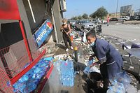 Women clear the damage on August 5, 2020 outside a sideroad kiosk in Beirut damaged by the previous day's massive explosion that tore through Lebanon's capital, resulting from the ignition of a huge depot of ammonium nitrate at the city's main port. - Rescuers searched for survivors in Beirut after a cataclysmic explosion at the port sowed devastation across entire neighbourhoods, killing more than 100 people, wounding thousands and plunging Lebanon deeper into crisis. The blast, which appeared to have been caused by a fire igniting 2,750 tonnes of ammonium nitrate left unsecured in a warehouse, was felt as far away as Cyprus, some 150 miles (240 kilometres) to the northwest. (Photo by STR / AFP)
