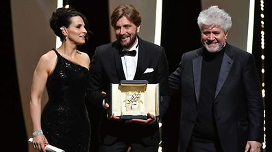 Le réalisateur suédois Ruben Ostlund (au centre), l'actrice française Juliette Binoche et le réalisateur espagnol Pedro Almodovar.