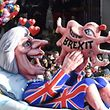People look at a carnival float, depicting Britain's Prime Minister Theresa May giving birth to the Brexit, during a carnival parade on Rose Monday on February 12, 2018 in Duesseldorf, western Germany. / AFP PHOTO / PATRIK STOLLARZ
