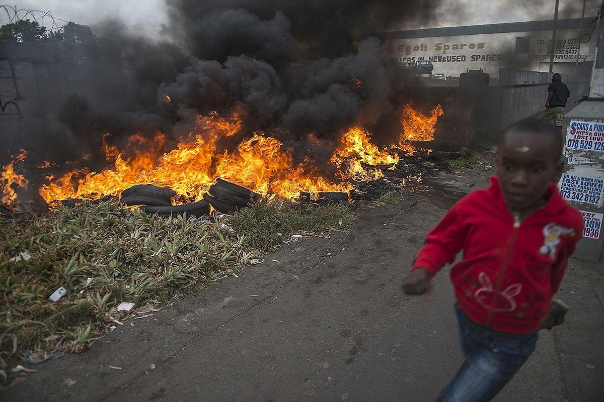 Ein Kind versucht sich, vor der Zerstörungswut der Zulu, in Sicherheit zu bringen. Nach lokalen Berichten zufolge, forderten die Protestierenden, dass Auslandsangehörige Südafrika verlassen.