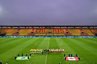 "Brazil's and Canada's players line up in an empty stadium prior to the 2020 ""Tournoi de France"" women's football tournament match between Brazil and Canada, held behind closed doors due to the spread of COVID-19, the new coronavirus, at the Epopee Stadium in Calais, northern France, on March  10, 2020. (Photo by DENIS CHARLET / AFP)"