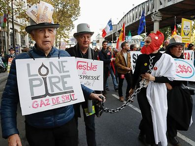 A person wearing a Phrygian cap walks with a chain hold by other in costumes during a demonstration for the protection of agriculture and against the Tafta and Ceta trade agreements on October 15, 2016 in Paris. Several hundred people demonstrated on October 15, 2016 afternoon in Paris to denounce the Ceta, the free trade agreement between EU and Canada, to be signed on October 27. Protesters were also mobilized against the Tafta (or TTIP), the free trade agreement project with the United States, whose scope is much larger but whose conclusion is no longer considered for this year. / AFP PHOTO / FRANCOIS GUILLOT