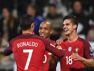 Portugal's forward Andre Silva (R) is cogratulated by teammates midfielder Joao Mario (C) and forward Cristiano Ronaldo after scoring a goal during the WC 2018 football qualification match between Faroe Islands and Portugal in Torshavn on October 10, 2016.  / AFP PHOTO / FRANCISCO LEONG