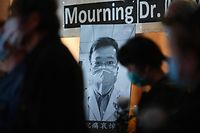 People attend a vigil in Hong Kong on February 7, 2020 for novel coronavirus whistleblowing doctor Li Wenliang (pictured background C), 34,�who died in Wuhan after contracting the virus while treating a patient. - A Chinese doctor who was punished after raising the alarm about China's new coronavirus died from the pathogen on February 7, sparking an outpouring of grief and anger over a worsening crisis that has now killed more than 630 people. (Photo by Anthony WALLACE / AFP)