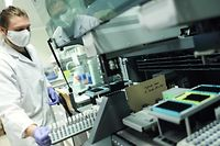 A researcher from the University of Liege analyses virological saliva samples for Covid-19 detection at the University of Liege, on October 14, 2020. - These tests, developed by the students of Liege university, have been used sucessfully by the University hospital. The purpose of this test, for which the patient collects their own sample, aims at decongesting testing centres. (Photo by Kenzo TRIBOUILLARD / AFP)