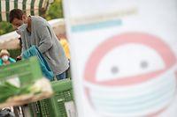 08.10.2020, Baden-Württemberg, Esslingen am Neckar: Eine Frau steht mit Mund- und Nasenschutz auf einem Markt im Stadtteil Oberesslingen hinter einem Schild, das auf den Mundschutz hinweist. Der Landkreis Esslingen als überschreitet als erste Region in Baden-Württemberg die kritische 50er-Corona-Marke. Foto: Sebastian Gollnow/dpa +++ dpa-Bildfunk +++