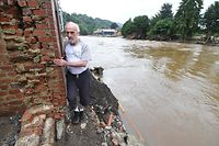 A local resident exits his house facing the destroyed and flooded road in Trooz, near Liege, on July 16, 2021. - The death toll from devastating floods in Europe soared to at least 126 on July 16, 2021, most in western Germany where emergency responders were frantically searching for missing people. In Belgium, the government confirmed the death toll had jumped to 20 - earlier reports had said 23 dead - with more than 21,000 people left without electricity in one region. (Photo by JOHN THYS / AFP)