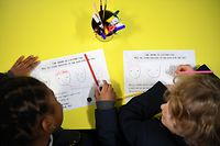Year 2 primary school students sit at their desks at Halley House School in east London, on March 8, 2021 as schools reopen following the easing of England's third coronavirus lockdown restrictions. - Millions of children returned to school in England on Monday for the first time in two months, with the government beginning to ease coronavirus restrictions as a mass vaccination drive ramps up. (Photo by DANIEL LEAL-OLIVAS / AFP)