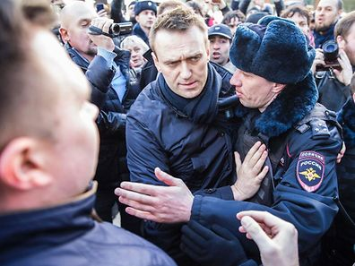 """TOPSHOT - This handout picture taken and provided by Evgeny Feldman for Alexei Navalny's campaign on March 26, 2017 shows police officers detaining Kremlin critic Alexei Navalny during an unauthorised anti-corruption rally in central Moscow. / AFP PHOTO / Evgeny Feldman for Alexei Navalny's campaign / HO / RESTRICTED TO EDITORIAL USE - MANDATORY CREDIT """"AFP PHOTO / Evgeny Feldman for Alexei Navalny's campaign"""" - NO MARKETING NO ADVERTISING CAMPAIGNS - DISTRIBUTED AS A SERVICE TO CLIENTS"""