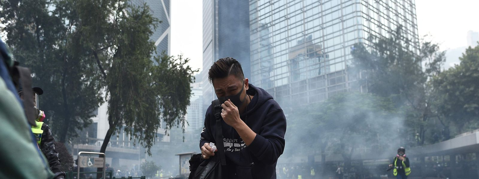 People react from tear gas fired by police to disperse the crowd gathered for the 'universal siege on communists' rally at Chater Garden in Hong Kong on January 19, 2020. - Violence returned to Hong Kong's streets on January 19 with police firing tear gas to disperse crowds after a group of officers were beaten bloody by pro-democracy protesters. Thousands of people had gathered in the city's commercial district for a sanctioned rally calling for greater democratic freedoms and police accountability, the latest in seven months of protests that have upended the financial hub. (Photo by Philip FONG / AFP)