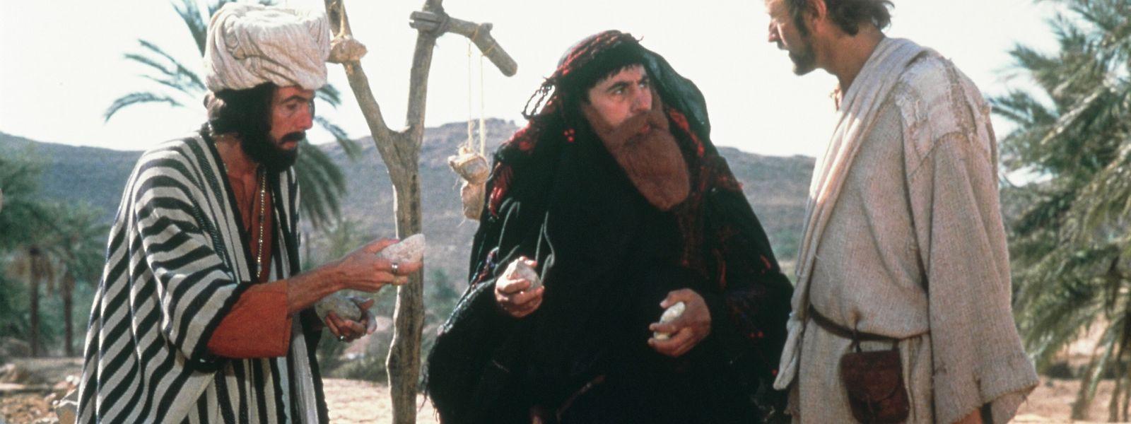 Vor der für Frauen eigentlich verbotenen Steinigung deckt sich die mit falschen Bart ausgestattete Mutter Mandy (Terry Jones, M.) und ihr Sohn Brian (Graham Chapman, r.) beim Händler (Eric Idle, l.) mit dem perfekten Geschoss ein.