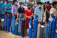This picture taken on July 14, 2021 shows people waiting to fill empty oxygen canisters at a location donating oxygen at no cost in Yangon, amid a surge in the number of Covid-19 coronavirus cases. - Residents across Myanmar's biggest city are defying a military curfew in a desperate search for oxygen to keep their loved ones breathing as a new coronavirus wave crashes over the coup-wracked country. (Photo by Ye Aung THU / AFP) / TO GO WITH Myanmar-health-virus-oxygen, FOCUS