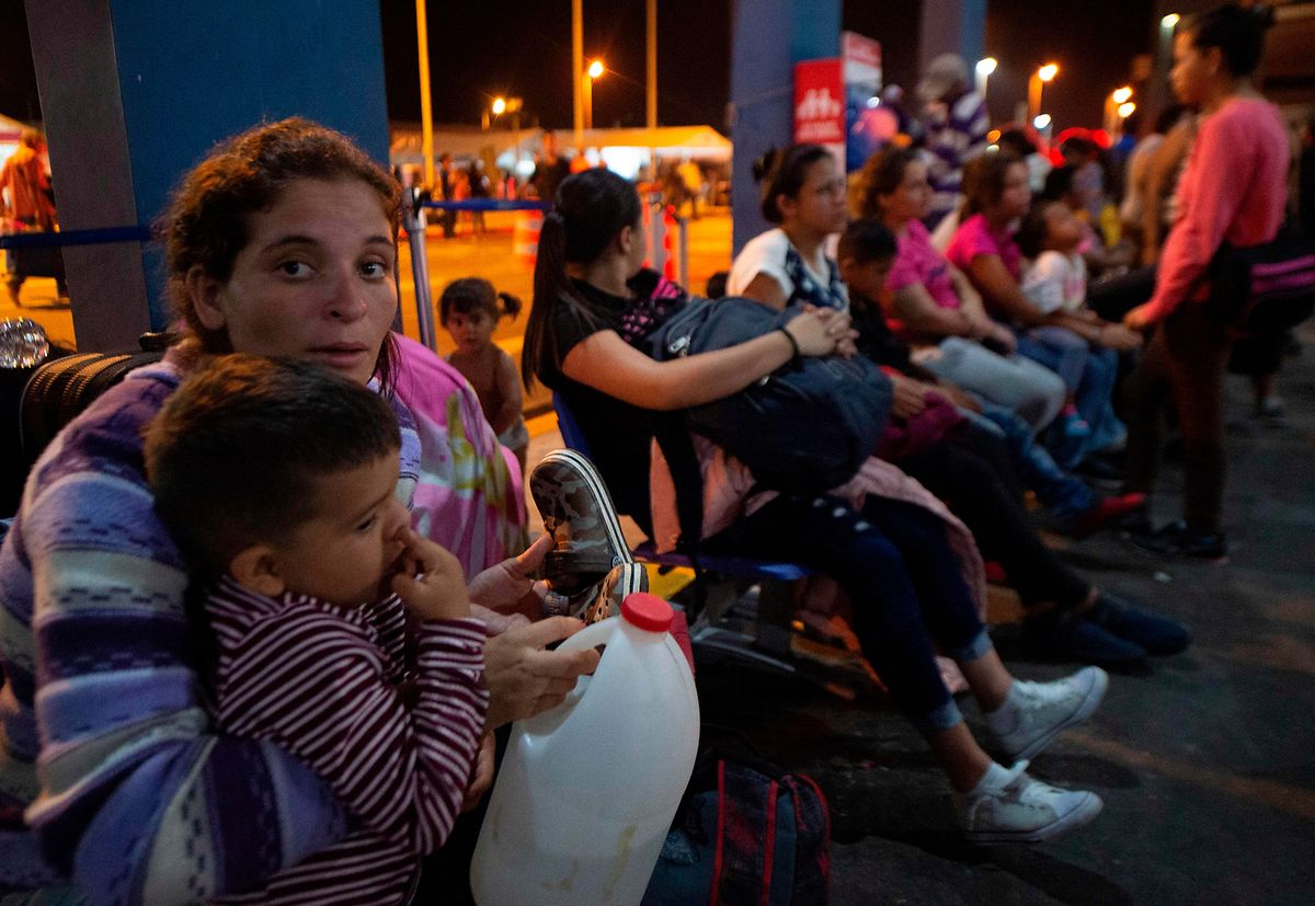 Cidadãos venezuelanos esperam na fila para receber um pedido de asilo no Peru