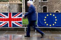 """A pedestrian walks past the Union (L) and EU flags of anti-Brexit activists near the Houses of Parliament in London on March 18, 2019. - Britain's government cannot submit its Brexit deal for another vote in parliament if it is """"the same"""" or """"substantially the same"""" to the one already rejected by MPs, the House of Commons speaker said on Monday. """"What the government cannot legitimately do is to re-submit to the House the same proposition or substantially the same proposition,"""" John Bercow told parliament. (Photo by Niklas HALLE'N / AFP)"""