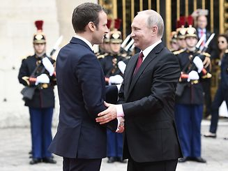 Russian President Vladimir Putin (R) is welcomed by French President Emmanuel Macron (L) as they shake hands at the Versailles Palace, near Paris, on May 29, 2017, ahead of their meeting. French President Emmanuel Macron hosts Russian counterpart Vladimir Putin in their first meeting since he came to office with differences on Ukraine and Syria clearly visible. / AFP PHOTO / STEPHANE DE SAKUTIN