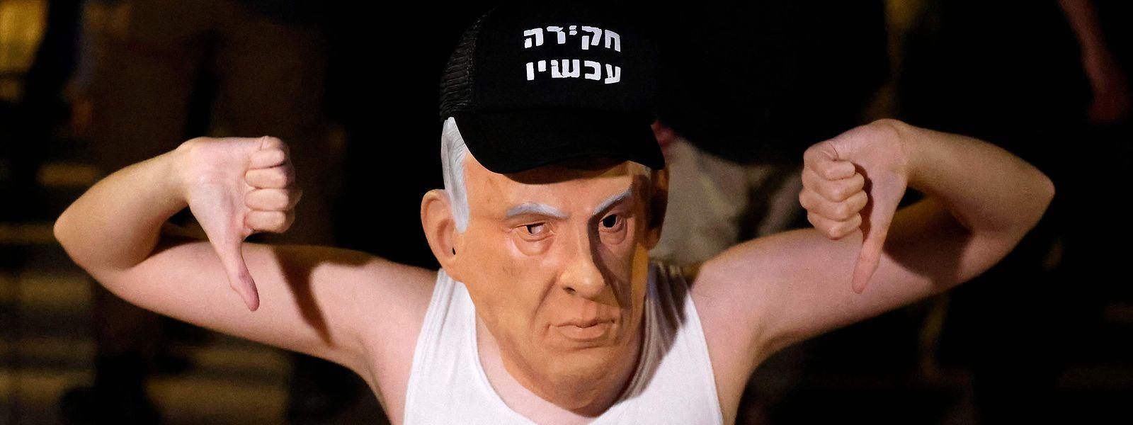 """Bei einer Protestkundgebung in Tel Aviv trägt ein Teilnehmer eine Netanjahu-Maske und ein T-Shirt, auf dem zu lesen ist: """"Die Zeremonie ist vorbei""""."""