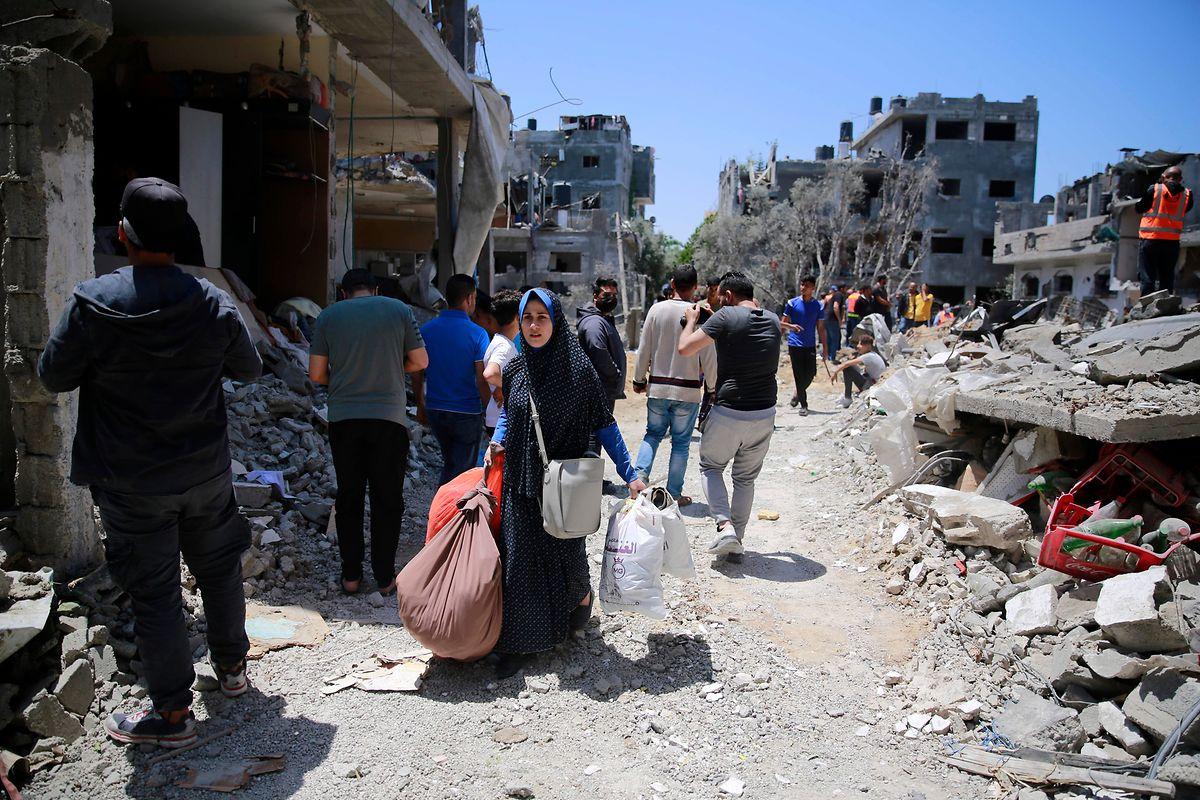 Eine palästinensische Frau in Gaza trägt ihre Habseligkeiten mit sich, nachdem ihr Haus nach israelischen Luft- und Artillerieangriffen beschädigt wurde.