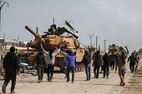 TOPSHOT - Syrians in protest surround a Turkish military M60T tank as they attempt to block traffic on the M4 highway, which links the northern Syrian provinces of Aleppo and Latakia, before incoming joint Turkish and Russian military patrols (as per an earlier agreed upon ceasefire deal) in the village of al-Nayrab, about 14 kilometres southeast of the city of Idlib and seven kilometres west of Saraqib in northwestern Syria on March 15, 2020. - Russian President Vladimir Putin and his Turkish counterpart Recep Tayyip Erdogan reached a deal on March 5 to create a security corridor with joint Turkish and Russian patrols starting on March 15 along the key M4 highway in northern Syria, which runs roughly parallel to the border with Turkey, from northeastern Kurdish-controlled regions to the Mediterranean coast. (Photo by AAREF WATAD / AFP)