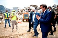French President Emmanuel Macron (R) salutes as he arrives to visit the devastated site of the explosion at the port of Beirut, on August 6, 2020 two days after a massive explosion devastated the Lebanese capital in a disaster that has sparked grief and fury. - French President Emmanuel Macron visited shell-shocked Beirut on August 6, pledging support and urging change after a massive explosion devastated the Lebanese capital in a disaster that left 300,000 people homeless. (Photo by Thibault Camus / POOL / AFP)