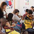 Irène Chatzisavas (links), eine der OPL-Violinistinnen, gibt Flüchtlingskindern in der Klasse von Giannis Ismirnioglou (hinten) Tipps.