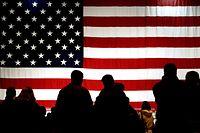 ARCHIV - 22.02.2005, Hessen, Ramstein: Besucher stehen auf der Air Base in Ramstein vor einer US-Flagge im Gegenlicht. Mit 35 000 US-Soldaten gilt Deutschland als wichtigster Stützpunkt der USA in Europa. Nun droht Präsident Trump mit einem Teilabzug. Das hätte auch massive wirtschaftliche Folgen. (zu dpa «Trotz und Trauer wegen Trump: Kommunen fürchten Abzug von US-Soldaten» vom 28.06.2020) Foto: Frank May/dpa +++ dpa-Bildfunk +++