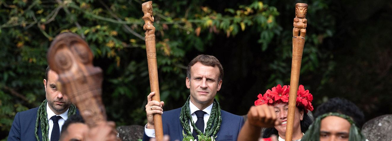 TOPSHOT - French President Emmanuel Macron attends a dance ceremony at the archaeological site of Upeke, on Hiva Oa island, the second largest island of the Marquesas Island, in French Polynesia on July 26, 2021. (Photo by Jacques WITT / POOL / AFP)