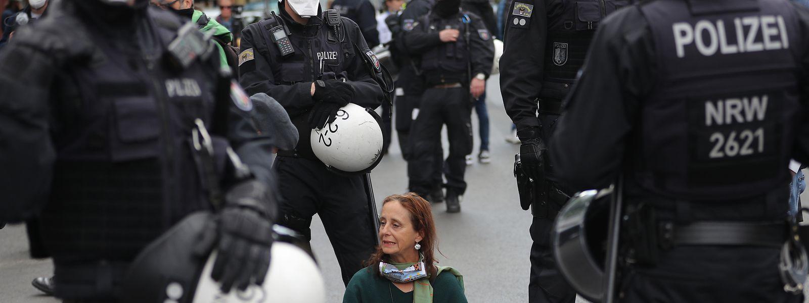 Eine von Polizisten umringte Frau sitzt in Berlin am Rande einer Demonstration zum 1. Mai.