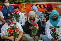 People from various religions gather to offer prayers for the 53 sailors trapped in the submarine in Surabaya on April 25, 2021, as Indonesia's military confirmed that all 53 crew were dead. (Photo by Juni Kriswanto / AFP)