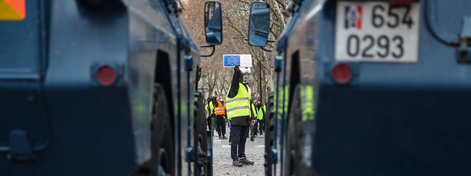 """Un """"gilet jaune"""" aperçu au loin, avec en premier plan deux véhicules blindés de la gendarmerie, près de l'Arc de Triomphe à Paris."""
