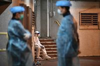 Medical personnels wearing protective suits stay near a block's entrance in the ground of a residential estate, in Hong Kong, early on February 11, 2020, after two people in the block were confirmed to have contracted the coronavirus according to local newspaper reports. (Photo by Anthony WALLACE / AFP)