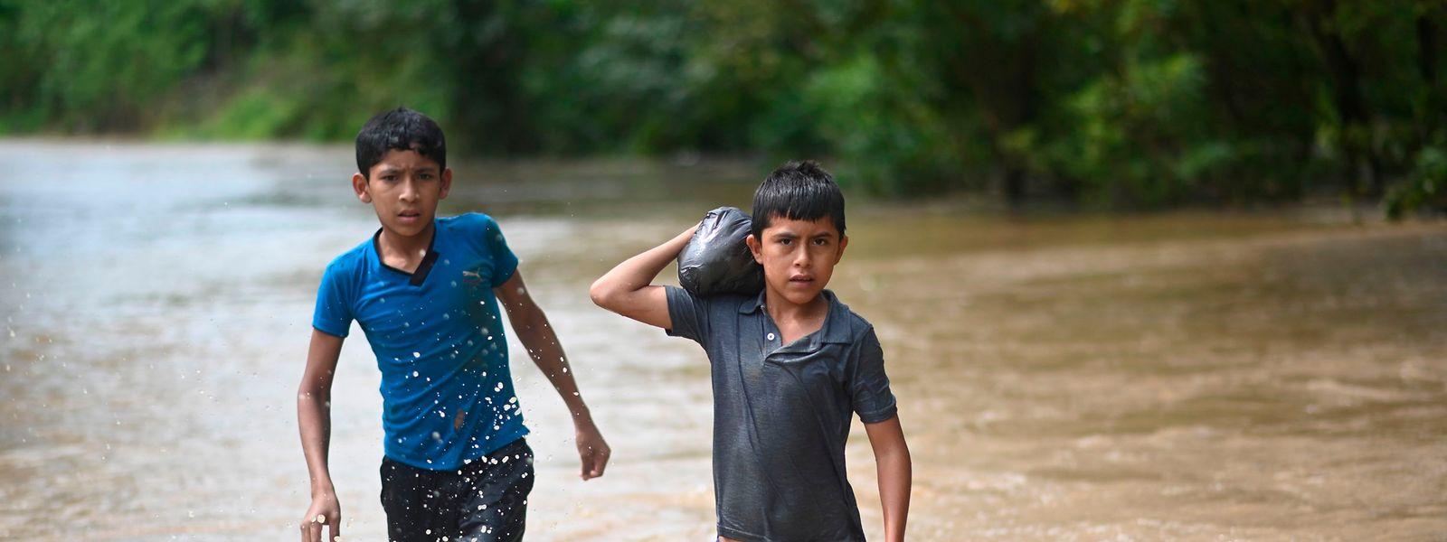 November 2020: Zwei Jungen waten durch überschwemmtes Land nördlich von Guatemala City nach dem Hurrikan Eta. 1,2 Millionen Kinder in der Region sind von der Katastrophe betroffen, schätzt die Unicef.