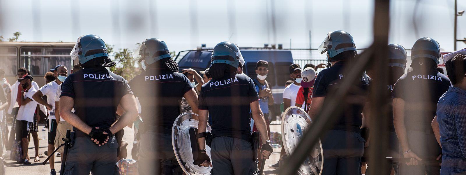 Italienische Polizisten stehen vor einer Gruppe tunesischer Migranten, die versuchten, das Aufnahmezentrum in Porto Empedocle zu verlassen.