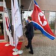 A staff of the International Olympic Committee (IOC) puts a North Korean flag back after it fell prior the North and South Korean Olympic Participation Meeting at the IOC headquarters on January 20, 2018 in Pully near Lausanne. Representatives from the two Koreas meet with the International Olympic Committee officials to discuss North Korea's participation in next month's Winter Games in Pyeongchang, South Korea.  / AFP PHOTO / Fabrice COFFRINI