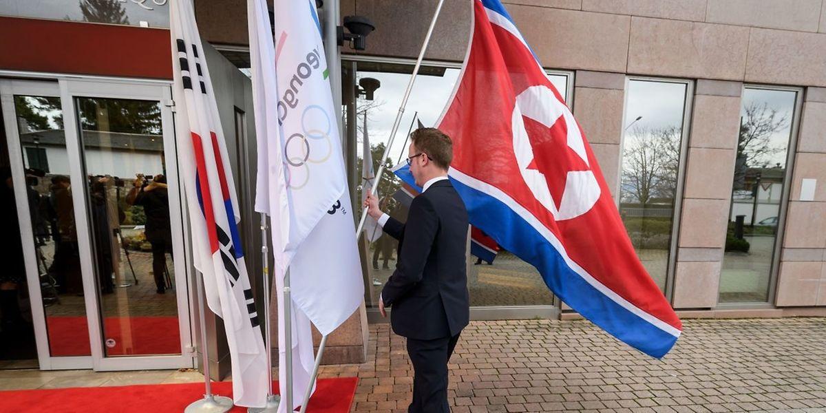 Eine nordkoreanische Flagge wird von einem Mitarbeiter des olympischen Komitees aufgestellt.