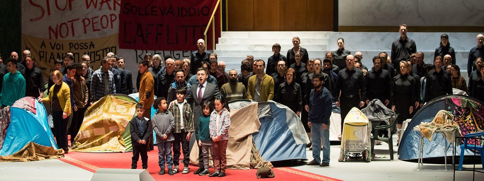 """Kinder von Geflüchteten, Mitglieder eines Projektchors mit Geflüchteten und Mitglieder des Chors der Hamburgischen Staatsoper stehen bei einer Fotoprobe zu """"Nabucco"""" auf der Bühne in der Staatsoper Hamburg."""