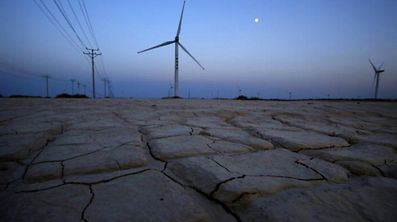 Cracked earth marks a dried-up area near a wind turbine used to generate electricity at a wind farm in Guazhou, 950km (590 miles) northwest of Lanzhou, Gansu Province, China