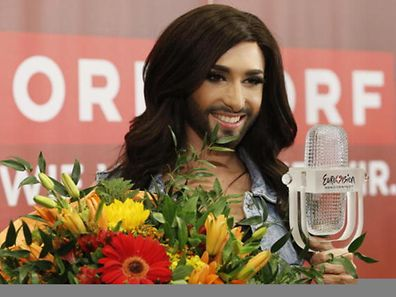 Austria's Conchita Wurst poses with her trophy and flowers after winning the 59th annual Eurovision Song Contest