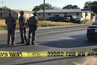 """TOPSHOT - Police block a road in Sutherland Springs, Texas, on November 5, 2017, after a mass shooting at the the First Baptist Church (rear). A gunman went into the church during Sunday morning services and shot dead some two dozen worshippers, the sheriff said, in the latest mass shooting to shock the US. """"Approximately 25 people"""" were dead, including the shooter, Wilson County Sheriff Joe Tackitt told NBC News. At least 10 people were wounded. The motive was not immediately known, he added.  / AFP PHOTO / SUZANNE CORDEIRO"""