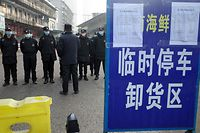 Security guards stand in front of the closed Huanan wholesale seafood market, where health authorities say a man who died from a respiratory illness had purchased goods from, in the city of Wuhan, Hubei province, on January 12, 2020. - A 61-year-old man has become the first person to die in China from a respiratory illness believed caused by a new virus from the same family as SARS, which claimed hundreds of lives more than a decade ago, authorities said. (Photo by Noel Celis / AFP)