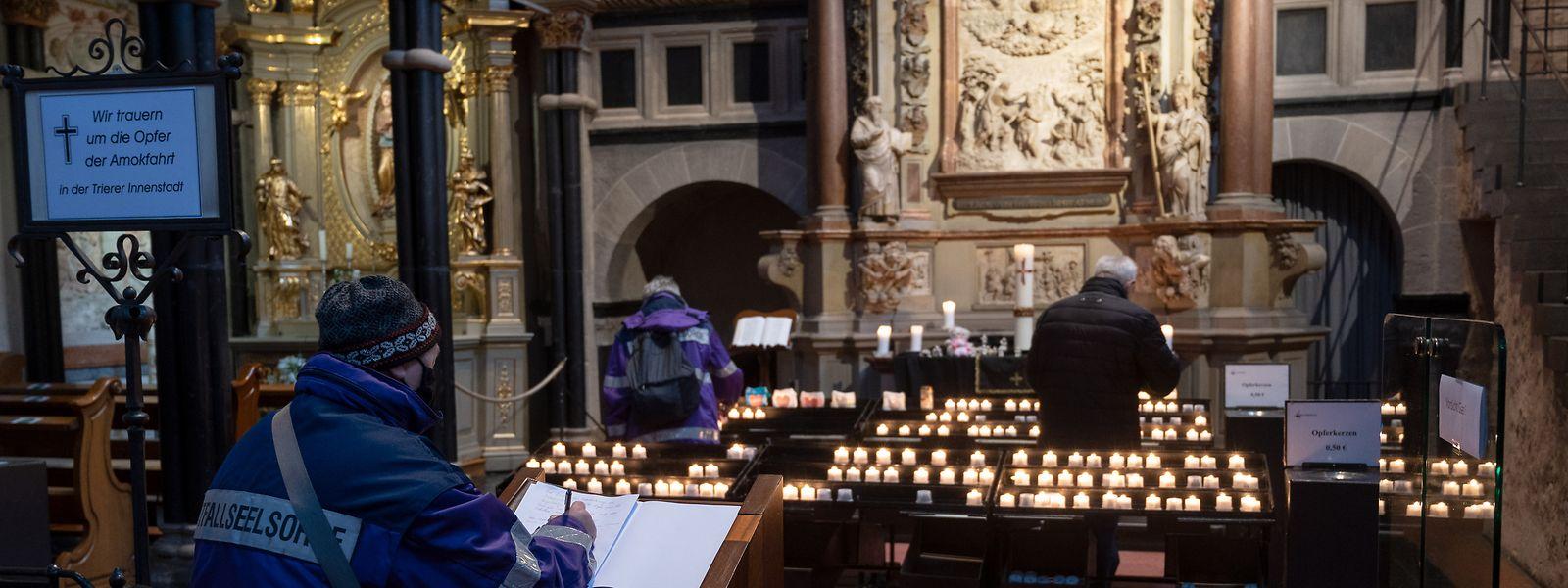 Menschen kondolieren im Dom zum Gedenken der Opfer nach der Amokfahrt von Trier.