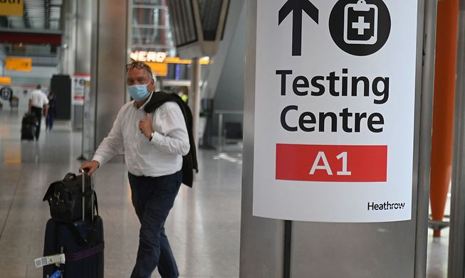 A passenger walks past signage displaying the way to a Covid-19 test centre, in Terminal 5 at Heathrow airport in London, on June 3, 2021.