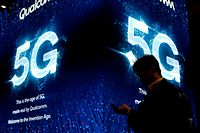 (FILES) In this file photo taken on February 27, 2019 a man uses his phone next to a 5G sign at the Qualcomm stand at the Mobile World Congress (MWC) in Barcelona. - Germany launches the auction on March 19, 2019 for the construction of an ultra-fast 5G mobile network while a transatlantic dispute rages about security concerns surrounding Chinese equipment maker Huawei. (Photo by Pau Barrena / AFP)