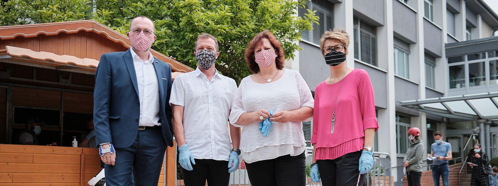 Bürgermeister Georges Engel und die Schöffen Mike Lorang, Simone Asselborn-Bintz und Nathalie Morgenthaler (v.l.n.r.) haben bei der Maskenverteilung vor dem Rathaus in Beles geholfen.
